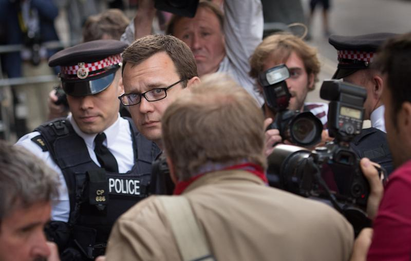 Former News of the World editor Andy Coulson, centre, arrives at the Old Bailey court to receive his sentence, in London, Friday, July 4, 2014. Coulson, a onetime aide to British Prime Minister David Cameron, was sentenced to 18 months in jail Friday for participating in a conspiracy to hack the phones of celebrities, politicians and crime victims. (AP Photo/PA, Stefan Rousseau) UNITED KINGDOM OUT