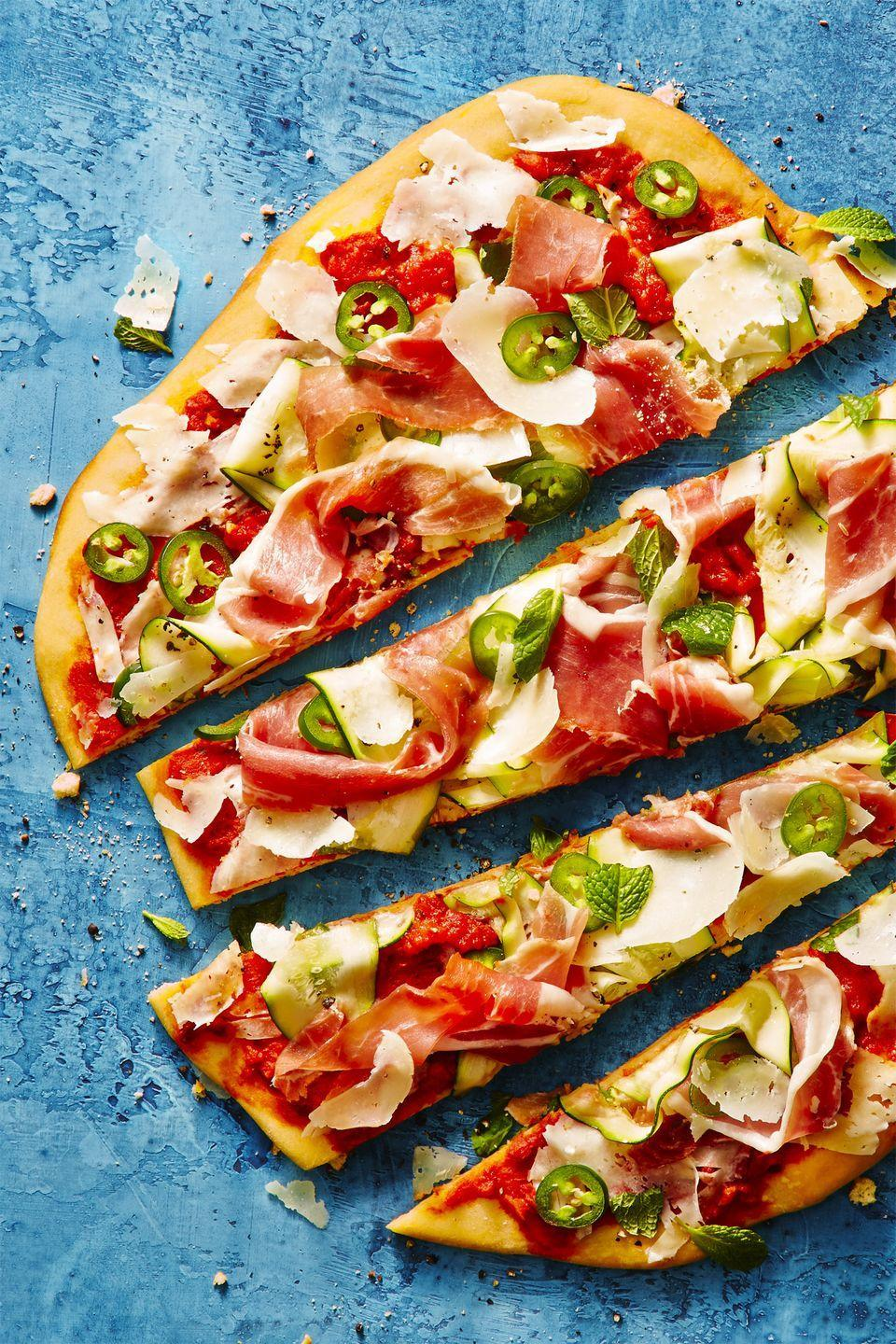 """<p>This pizza, topped with salty ham and fresh veg, simply looks like summer (and tastes like it, too). </p><p><a href=""""https://www.goodhousekeeping.com/food-recipes/a44186/shaved-zucchini-prosciutto-grilled-pizza-recipe/"""" rel=""""nofollow noopener"""" target=""""_blank"""" data-ylk=""""slk:Get the recipe for Grilled Zucchini-Prosciutto Pizza »"""" class=""""link rapid-noclick-resp""""><em>Get the recipe for Grilled Zucchini-Prosciutto Pizza »</em></a> </p>"""