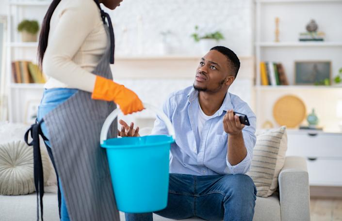Lazy black man watching TV while his wife doing home cleanup, having fight with her, not wanting to help, indoors. Idle African American guy arguing with his exhausted girlfriend about house chores