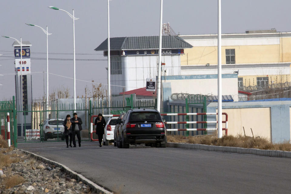 FILE - In this Dec. 3, 2018, file photo, people walk by a police station by the front gate of the Artux City Vocational Skills Education Training Service Center in Artux in western China's Xinjiang region. U.S. Customs and Border Protection say officers have detained a shipment of beauty supplies including weaves suspected to be made with human hair that originated in Xinjiang, China. Border Protection tells The Associated Press it seized the shipment Wednesday in New York because the weaves appear to be a product of forced child labor and imprisonment. Twice this year U.S. Customs has banned imports of hair weaves believed to be made by people locked inside Chinese detention camps. (AP Photo/Ng Han Guan, File)