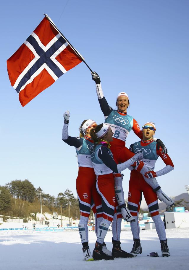 Cross-Country Skiing - Pyeongchang 2018 Winter Olympics - Women's 30km Mass Start Classic - Alpensia Cross-Country Skiing Centre - Pyeongchang, South Korea - February 25, 2018 - Winner Marit Bjoergen of Norway waves the Norwegian flag as she is carried by her teammates. REUTERS/Carlos Barria