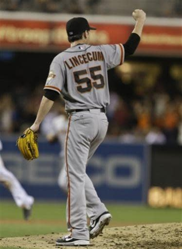 San Francisco Giants starting pitcher Tim Lincecum lifts a fist toward Giants right fielder Hunter Pence after Pence made a diving catch to save Lincecum's no hitter against the San Diego Padres in the eighth inning of a baseball game in San Diego, Saturday, July 13, 2013. (AP Photo/Lenny Ignelzi)