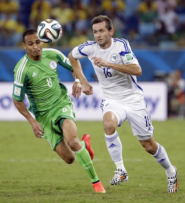 Nigeria's Peter Odemwingie, left, chases the ball with Bosnia's Senad Lulic during the group F World Cup soccer match between Nigeria and Bosnia at the Arena Pantanal in Cuiaba, Brazil, Saturday, June 21, 2014. (AP Photo/Felipe Dana)