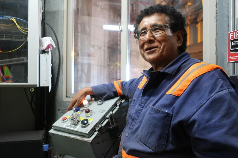 In this Aug. 20, 2019, image, Peabody Energy silo operator Gerald Clitso talks with coworkers after loading coal into a train bound for the Navajo Generating Station near Page, Ariz. The power plant will close before the year ends, upending the lives of hundreds of mostly Native American workers who mined coal, loaded it and played a part in producing electricity that powered the American Southwest. (AP Photo/Felicia Fonseca)