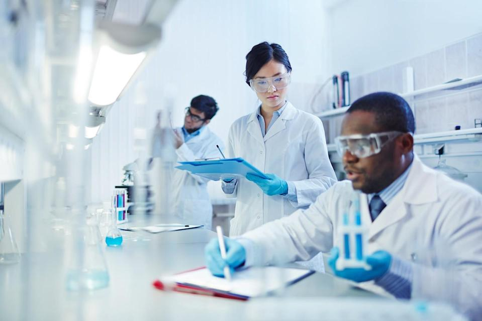 three scientists working in a laboratory wearing goggles and white coats