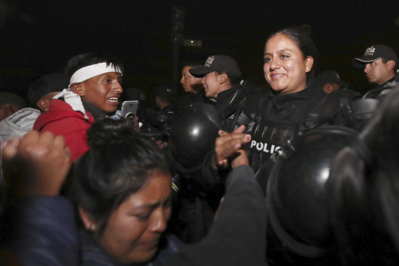 Indigenous and protesters celebrate with policemen the announcement that the government cancelled an austerity package that triggered violent protests, in Quito, Ecuador, Sunday, Oct. 13, 2019. Ecuadorian President Lenin Moreno and leaders of the country's indigenous peoples have struck a deal to cancel the disputed austerity package and end nearly two weeks of protests that have paralyzed the economy and left several people dead. (AP Photo/Dolores Ochoa)