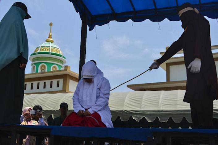 An Indonesian woman is whipped by a member of the Sharia police in Banda Aceh (AFP Photo/CHAIDEER MAHYUDDIN)