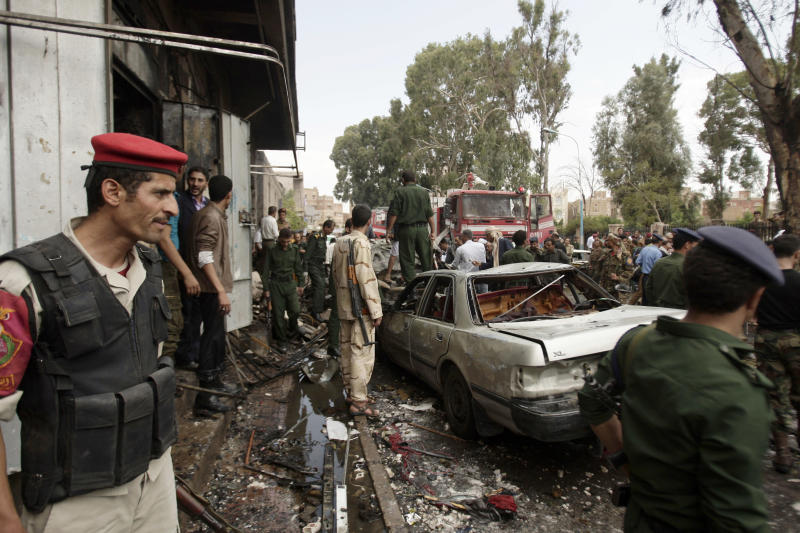 Yemeni soldiers gather at the site of a car bomb attack targeting the motorcade of the country's defense minister in Sanaa, Yemen, Tuesday, Sept. 11, 2012. Yemeni officials say a car bomb targeting the motorcade of the country's defense minister has killed several people, but the minister escaped unharmed. (AP Photo/Hani Mohammed)