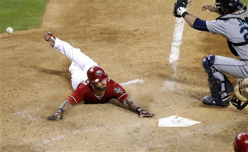Arizona Diamondbacks' Ryan Roberts dives for home plate after hitting an inside-the-park home run during the sixth inning of an interleague baseball game as Seattle Mariners catcher John Jaso can't get a glove on the ball, Wednesday, June 20, 2012, in Phoenix. (AP Photo/Matt York)