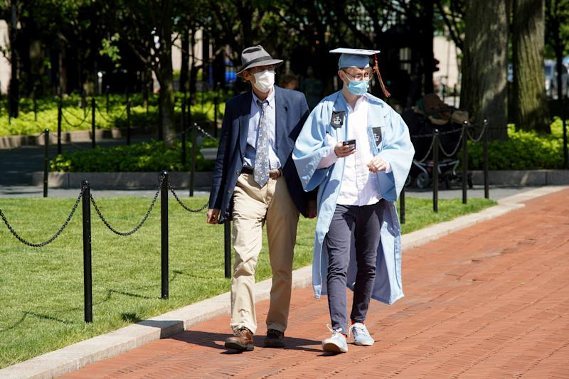 NEW YORK, NEW YORK - MAY 21: A graduate wearing a cap, gown and protective face mask is seen on the campus of Columbia University on May 21, 2020 in New York City. COVID-19 has spread to most countries around the world, claiming over 332,000 lives with infections of over 5.1 million people. (Photo by Rob Kim/Getty Images)