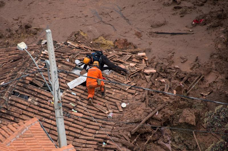 Firemen on a shattered rooftop search for survivors after a dam at a mining waste site burst, smothering the village of Bento Rodrigues, Brazil, on November 6, 2015 (AFP Photo/Christophe Simon)