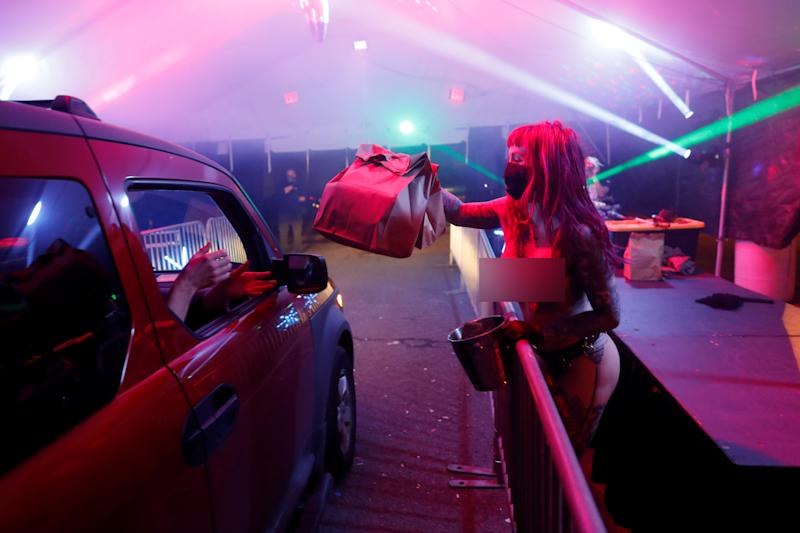 Dancer Elle Stanger serves takeaway food in coronavirus protective equipment at Portland socially distant strip club