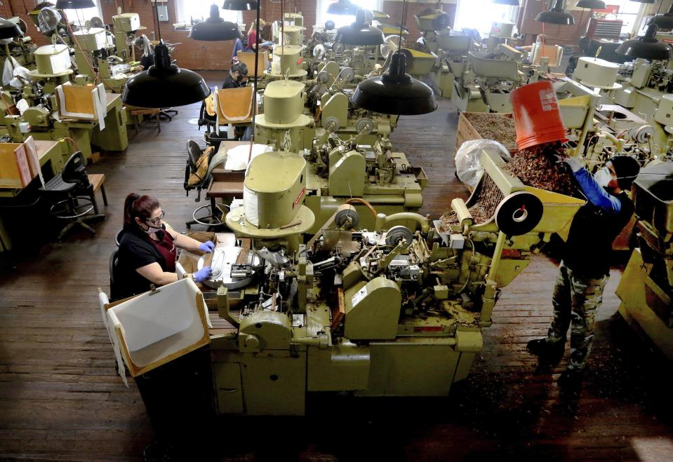 FILE - In this Dec. 14, 2020 file photo, Zeida Hernandez, of Tampa, Fla., left, makes Factory Throwout cigars using an antique hand-operated cigar machine at the J.C. Newman Cigar Co., Tampa's last cigar factory, in Fla. American factories grew in December at the fastest pace in more than two years as manufacturing continued to weather the pandemic better than the battered services sector. (Douglas R. Clifford/Tampa Bay Times via AP)