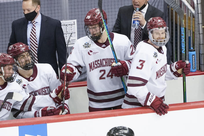 Massachusetts' Zac Jones (24) is greeted by teammates after scoring against Minnesota Duluth during the first period of an NCAA men's Frozen Four hockey semifinal in Pittsburgh, Thursday, April 8, 2021. (AP Photo/Keith Srakocic)