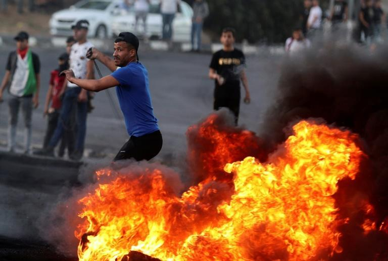 A Palestinian protester hurls rocks during confrontations with Israeli troops at the Hawara checkpoint south of the West Bank city of Nablus