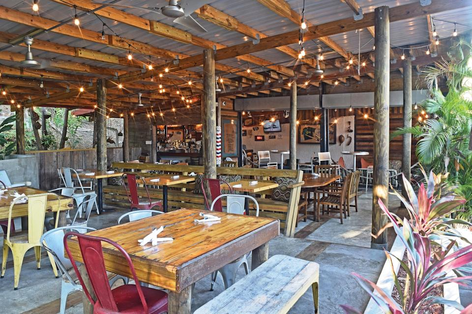 """<p><strong>What are your first impressions of this place as you arrive?</strong><br> The moment you walk into La Estación, a quirky gas station-turned-restaurant off the highway in Fajardo, you know you're in for a wild ride. It's a little tiki and a little industrial-chic, with indoor tables, outdoor tables, grungy automotive paraphernalia, and leafy jungle vibes. Plus, the whole place smells like <a href=""""https://www.cntraveler.com/gallery/best-bbq-in-austin?mbid=synd_yahoo_rss"""" rel=""""nofollow noopener"""" target=""""_blank"""" data-ylk=""""slk:Texas BBQ"""" class=""""link rapid-noclick-resp"""">Texas BBQ</a>.</p> <p><strong>What's the crowd like?</strong><br> An eclectic mix—old, young, locals, visitors—all losing their minds over the food.</p> <p><strong>What should we be drinking?</strong><br> A great selection of cocktails, from perfect classics (martinis, margaritas, mojitos) to inventive creations championing local flavors. We liked the Cocotazo, which tastes like the liquid version of tembleque (Puerto Rican coconut pudding), and the Fajardo Sunrise, a refreshing blend of tequila, local passionfruit, and guava.</p> <p><strong>On to the food. What does the kitchen do best?</strong><br> The food here is as eclectic as the restaurant itself—you'll find everything from delicate, bright, catch-of-the-day ceviches to fried chicken with mac 'n cheese. But the barbecue is the real showstopper: slow-cooked beef brisket, smoky, fall-off-the-bone ribs, and juicy pulled pork, all stuffed into a plantain """"canoe."""" The sampler, which comes with three meats, is a great way to go. The lechón is fabulous, too, although it's usually only made on special occasions and holidays. Almost all of the ingredients are sourced from local farmers.</p> <p><strong>And how were the front-of-house folks?</strong><br> Delightfully friendly and armed with honest, thoughtful recommendations.</p> <p><strong>Who should come to La Estación?</strong><br> This is easily the best barbecue spot on the island. Bring your """