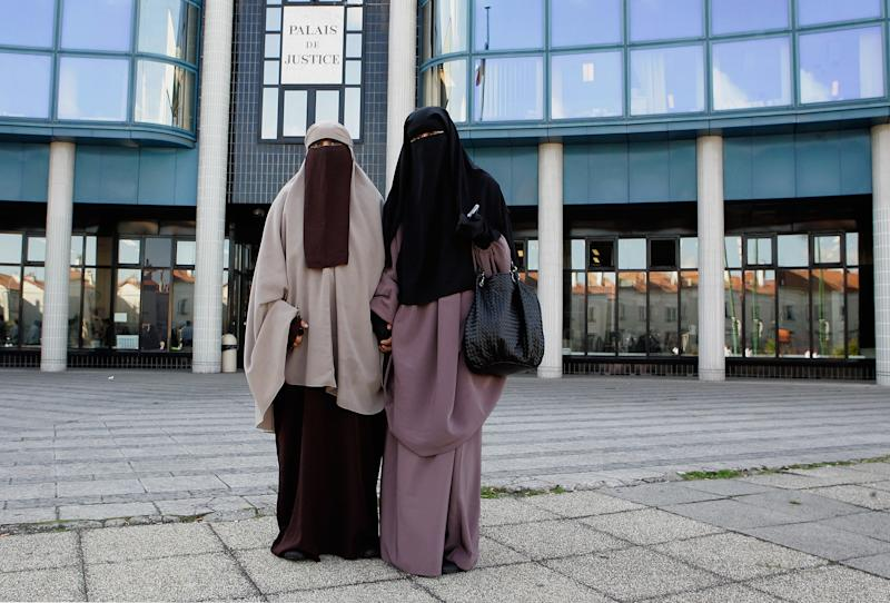 Hind Ahmas (right) stands with Kenza Drider as she leaves a court in Meaux, France, after facing fines for wearing a face veil on Sept. 22, 2011. (Franck Prevel via Getty Images)