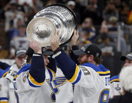 St. Louis Blues' Ryan O'Reilly, right, hands the Stanley Cup to Vladimir Tarasenko, left, of Russia, after the Blues defeated the Boston Bruins in Game 7 of the NHL Stanley Cup Final, Wednesday, June 12, 2019, in Boston. (AP Photo/Michael Dwyer)