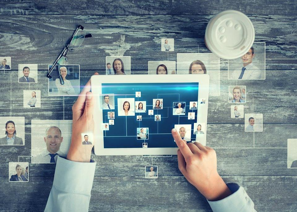 Ipad shows images of multiple people in a web to illustrate a social network