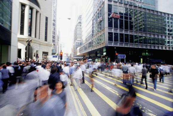 People walk down a busy street in a big city.