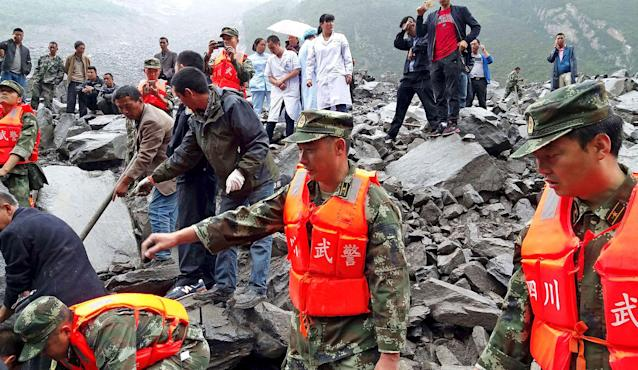 <p>Emergency personnel and local people work at the site of a landslide in Xinmo village in Maoxian County in southwestern China's Sichuan Province, Saturday, June 24, 2017. (Photo: Chinatopix via AP) </p>