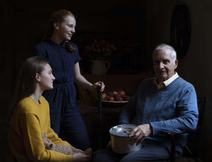 In this photo taken by Britain's Kate, Duchess of Cambridge and made available on Sunday Jan. 26, 2020, Steven Frank BEM, aged 84, originally from Amsterdam, who survived multiple concentration camps as a child, is pictured alongside his granddaughters Maggie and Trixie Fleet, aged 15 and 13. (The Duchess of Cambridge via AP)