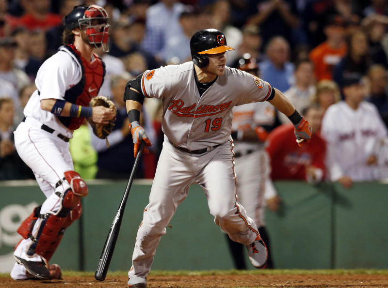 Baltimore Orioles' Chris Davis heads to first on a two-run single as Boston Red Sox catcher Jarrod Saltalamacchia watches during the 12th inning of a baseball game at Fenway Park in Boston, Wednesday, Sept. 18, 2013. The Orioles won 5-3 in 12 innings. (AP Photo/Elise Amendola)