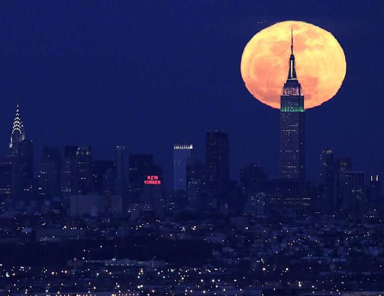 """FILE - A full moon rises behind the Empire State Building in New York in this view from Eagle Rock Reservation in West Orange, N.J., in this April 6, 2012 file photo. The biggest and brightest full moon of the year arrives Saturday night May 5, 2012 as our celestial neighbor passes closer to Earth than usual. Saturday's event is a """"supermoon,"""" the closest and therefore the biggest and brightest full moon of the year. At 11:34 p.m., the moon will be about 221,802 miles from Earth. That's about 15,300 miles closer than average. (AP Photo/Julio Cortez, File)"""