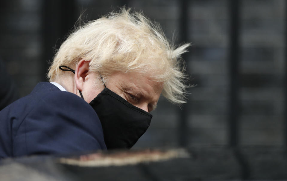 Prime Minister Boris Johnson leaves 10 Downing Street for the House of Commons wearing a mask.