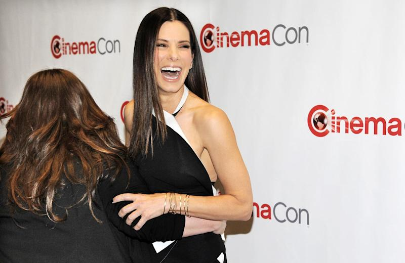 """Sandra Bullock, right, a cast member in the upcoming film """"The Heat,"""" laughs as she is grabbed by fellow cast member Melissa McCarthy backstage before 20th Century Fox's presentation at CinemaCon 2013 at Caesars Palace on Thursday, April 18, 2013 in Las Vegas. (Photo by Chris Pizzello/Invision/AP)"""