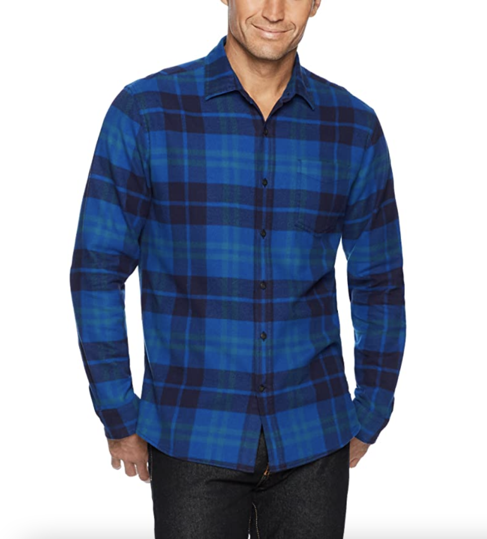 male model with head cut off posing in blue plaid shirt with black jeans and hands in pocket