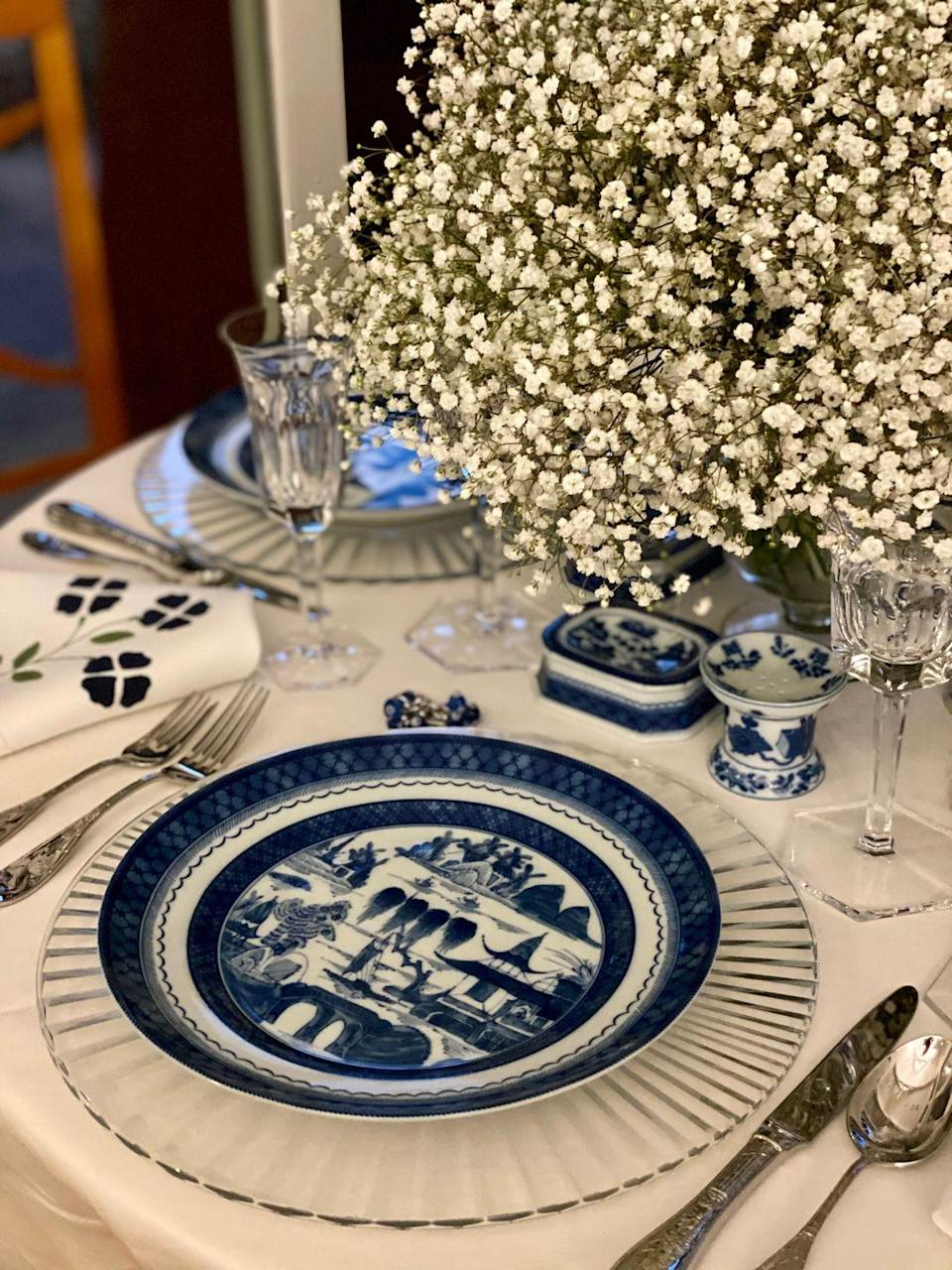 "<p>Simple elegance is the focus of this table designed by hostess extraordinaire <a href=""https://kimberlywhitman.com/"" rel=""nofollow noopener"" target=""_blank"" data-ylk=""slk:Kimberly Schlegal Whitman"" class=""link rapid-noclick-resp"">Kimberly Schlegal Whitman</a>. She says her family has enjoyed taking the time to set the table together throughout the pandemic to keep holidays (and weeknights!) feeling more special. </p><p>Here, Whitman uses her favorite blue-and-white canyon plates with faceted crystal chargers to bring a glamorous New Year's Eve element to the table. <a href=""https://elizabethlake.com/"" rel=""nofollow noopener"" target=""_blank"" data-ylk=""slk:Elizabeth Lake"" class=""link rapid-noclick-resp"">Elizabeth Lake</a> linens and <a href=""https://www.moser.com/"" rel=""nofollow noopener"" target=""_blank"" data-ylk=""slk:Moser"" class=""link rapid-noclick-resp"">Moser</a> crystal glassware bring an extra element of elevation. She also plans to include some table favors for a fun surprise. </p>"