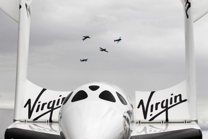 Seen in between the wings of the Virgin Galatica VSS Enterprise, the Blades aerobatics team fly in display during Farnborough International Airshow, Farnborough, England, Monday, July 9, 2012. (AP Photo/Sang Tan)