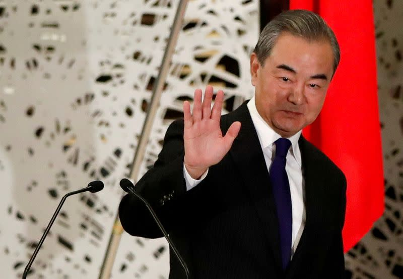 FILE PHOTO: China's State Councillor and Foreign Minister Wang Yi waves as he leaves a news conference in Tokyo, Japan