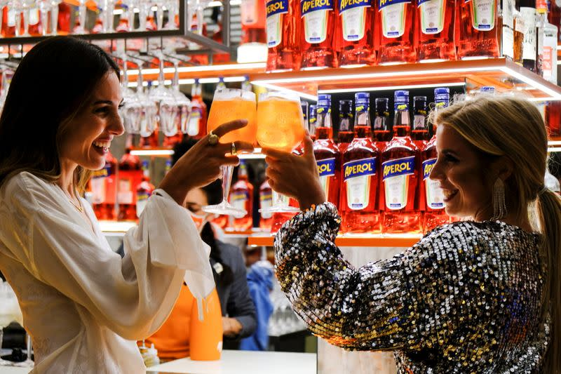 Women holding drinks attend a Campari inauguration of a new brand house for Aperol, its best-selling beverage, in Venice, Italy