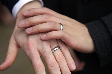 Bernie Liang and Ryan Hamachek show their rings after getting married outside Seattle City Hall
