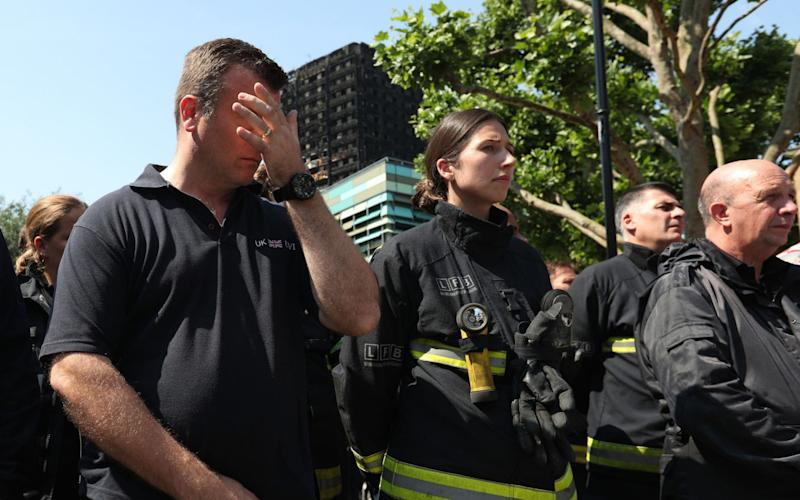 Members of the emergency services observe a minute's silence near to Grenfell Tower. - Credit: Jonathan Brady/PA Wire