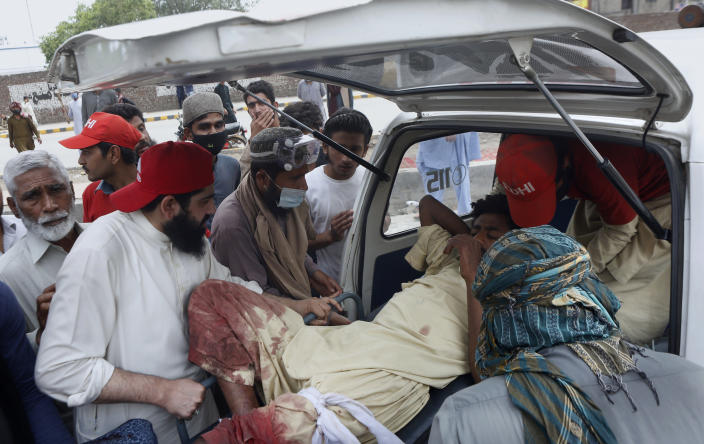 Supporters of Tehreek-e-Labiak Pakistan, a banned Islamist party, help load their injured colleague into an ambulance during a protest on the arrest of their party leader Saad Rizvi, who was demanding the government to expel French ambassador, in Lahore, Pakistan, Sunday, April 18, 2021. A crackdown by security forces on protesting supporters of the banned party left several people dead and many others, including police officers, injured, a police spokesman said Sunday. (AP Photo/K.M. Chaudary)