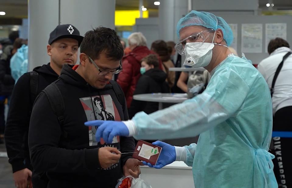 MOSCOW REGION, RUSSIA - MARCH 10, 2020: A video screen grab shows an employee in a protective suit at Terminal F, obliged to check passengers arriving from China, Italy, South Korea and Iran, ask them to fill in special forms and have their temperature measured upon arrival at Sheremetyevo International Airport, its health security measures tightened due to the COVID-19 outbreak. Press Office of the Moscow Healthcare Department/TASS (Photo by Moscow Healthcare Department\TASS via Getty Images)