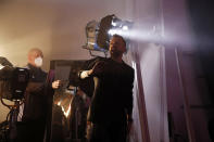 French designer Julien Fournie, right, gives instructions to the models, as general director Jean Paul Cauvin, left, looks on, during the shoot for his Haute Couture Spring/Summer 2021 fashion collection for a digital presentation of the fashion week, in Paris, Thursday, Jan. 7, 2021. With shows taking place behind closed doors due to the virus pandemic, some designers such as Julien Fournie are becoming versatile: Getting their designs out to the public by making a film of their collection and streaming it online. (AP Photo/Francois Mori)