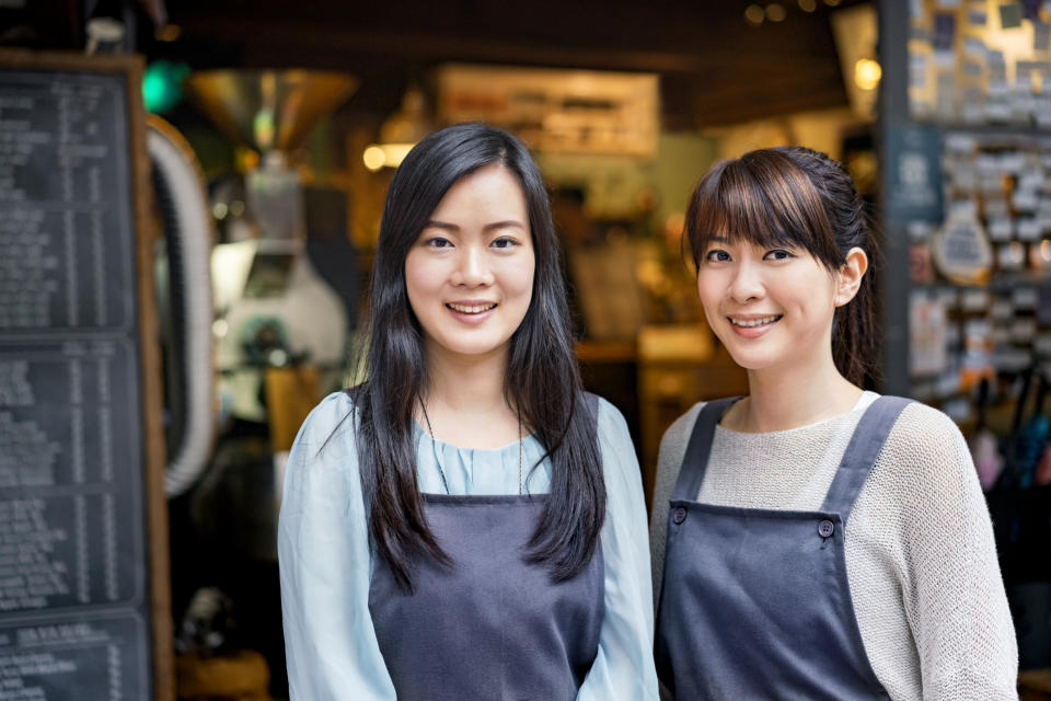 Portrait of smiling female cafe workers standing against coffee shop.