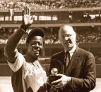 FILE - In this April 4, 1974, file photo, baseball commissioner Bowie Kuhn, right, presents Atlanta Braves' Hank Aaron with a trophy after he tied Babe Ruth's all-time home run record in Cincinnati. (AP Photo/Bob Johnson, File)