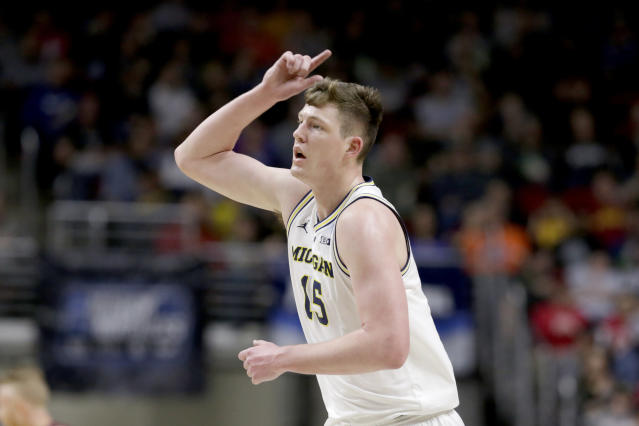 Michigan's Jon Teske (15) celebrates after scoring a three-point basket during the first half of a first round men's college basketball game against Montana in the NCAA Tournament in Des Moines, Iowa, Thursday, March 21, 2019. (AP Photo/Nati Harnik)
