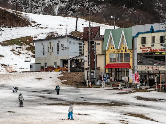Skiers pause near restaurants at a ski resort that has had to close a number of slopes because of a lack of snow in Minamiuonuma, Japan. Getty Images