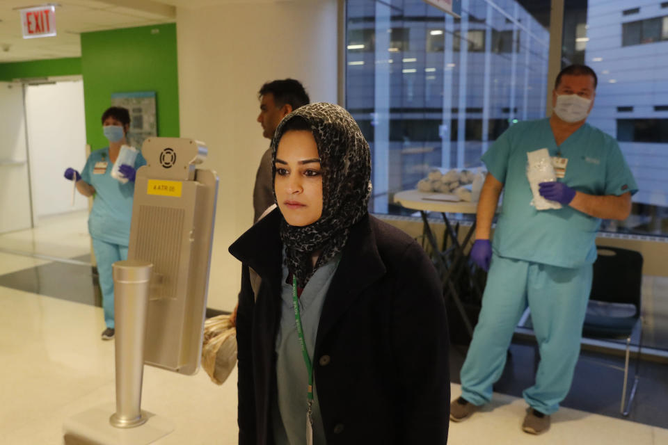 In this Wednesday, April 22, 2020, RUSH Hospital respiratory therapist Jumana Azam pauses before a face temperature scanner as she reports for her early morning shift at the hospital in Chicago. (AP Photo/Charles Rex Arbogast)