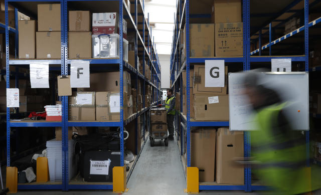 Lovespace warehouse worker Pawel Mazur places boxes into their allocated zones at the warehouse in Dunstable, England Monday, Jan. 14, 2019. Lovespace, which collects boxes from customers, stores them and then returns the goods when needed, says revenue from businesses doubled over the past year as enterprises large and small began stockpiling inventory because of concerns they will be cut off from suppliers if Britain leaves the European Union without an agreement on future trading relations. (AP Photo/Alastair Grant)