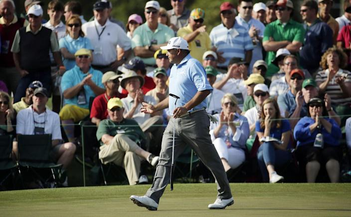 Angel Cabrera, of Argentina, waves to spectators as he walks up the 18th fairway during the second round of the Masters golf tournament Friday, April 11, 2014, in Augusta, Ga. (AP Photo/Charlie Riedel)
