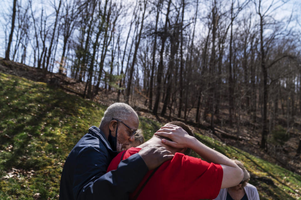 """Quick Response Team member pastor Fred McCarty, prays with a young man who recently overdosed as they visit him at his home in Barboursville, W.Va., Thursday, March 18, 2021. McCarty is one of the faith leaders who ride with the team. When they reach people who overdosed, he asks if they'd like him to pray with them, and usually they say yes. On his keychain he carries the coin he got in 1985, when he finished treatment for his own alcohol addiction. It says """"one day at a time,"""" and it's worn down from rubbing his finger across it for more than 30 years. """"Recovery is about sharing your strengths and hopes with others,"""" he said. """"Our hope is that a lightbulb will come on. And they'll say, if you can do it, I can do it."""" (AP Photo/David Goldman)"""