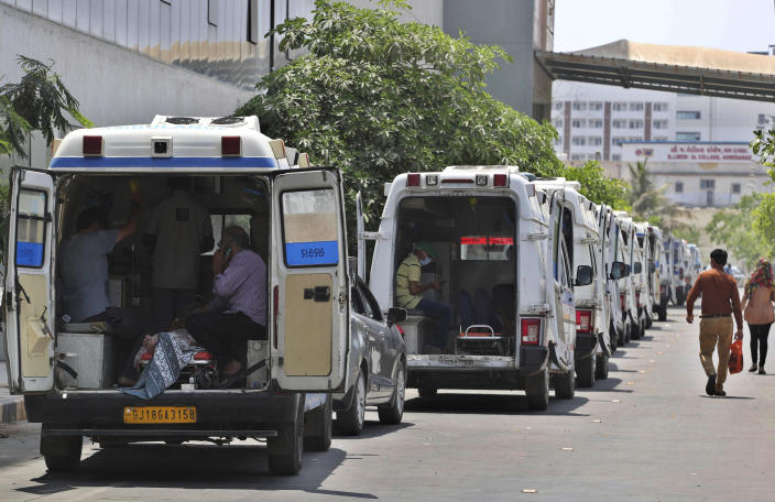 Ambulances carrying COVID-19 patients line up waiting for their turn to be attended to at a dedicated COVID-19 government hospital in Ahmedabad, India, Thursday, April 22, 2021. Indian authorities scrambled Saturday to get oxygen tanks to hospitals where COVID-19 patients were suffocating amid the world's worst coronavirus surge, as the government came under increasing criticism for what doctors said was its negligence in the face of a foreseeable public health disaster. (AP Photo/Ajit Solanki)