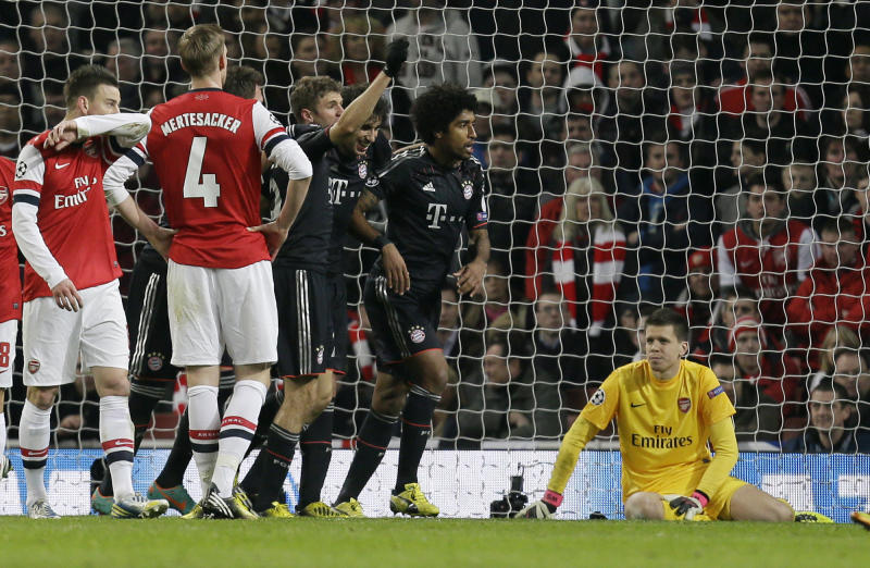 Arsenal goalkeeper Wojciech Szczesny, right, looks on as Bayern's Thomas Mueller, third left, celebrates scoring his side's 2nd goal during a Champions League, round of 16, first leg soccer match between Arsenal and Bayern Munich at Arsenal's Emirates stadium in London, Tuesday, Feb. 19, 2013.(AP Photo/Alastair Grant)